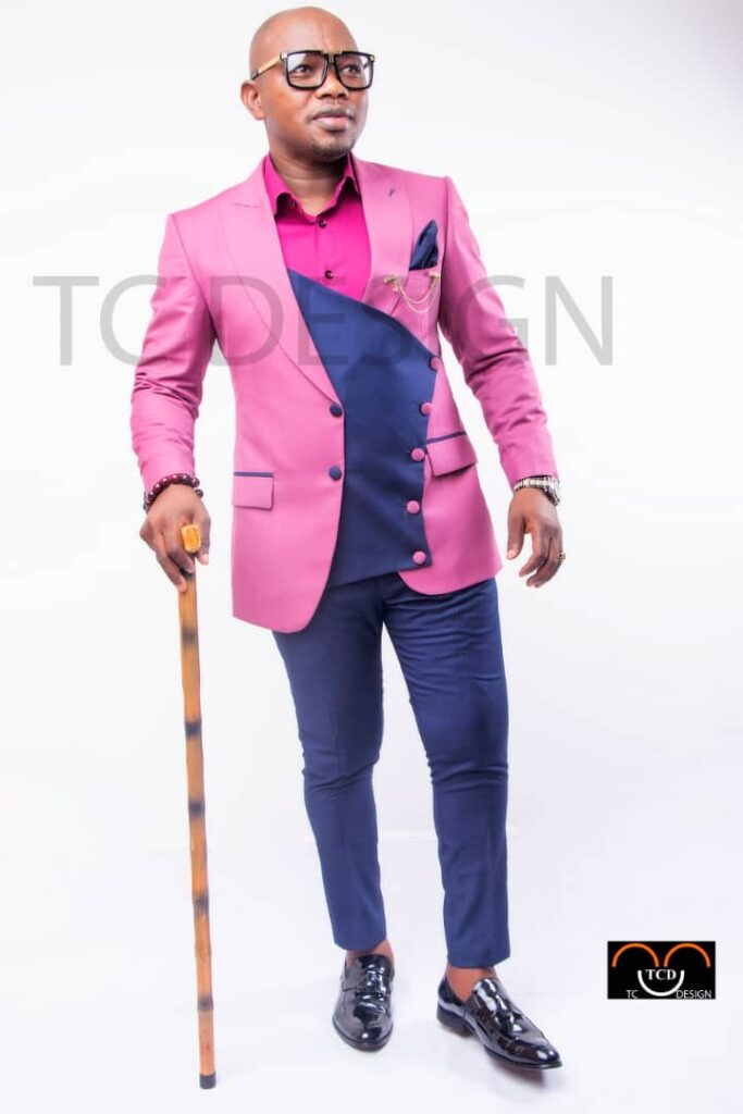 African man in pink suit, a stick, white background, in glasses, black shoes